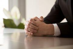 关闭在桌上一起握紧的男性被扣紧的手 免版税图库摄影