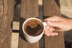 关闭在桌上的加奶咖啡杯子在早晨时间 免版税库存照片