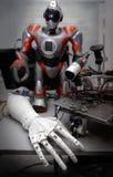 关闭在桌上的机器人手与另一个机器人和细节在背景 库存照片
