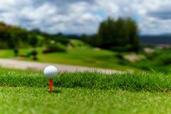关闭在橙色发球区域的白色山背景高尔夫球在与蓝天和云彩的绿草和看法在晴天 免版税图库摄影