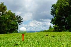 关闭在橙色发球区域的白色高尔夫球在与蓝天和云彩的绿草 复制您的文本的空间 免版税库存图片