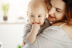 关闭在母亲手上的逗人喜爱的矮小的婴孩 看有爱和关心的妈妈孩子,当孩子咬手和微笑时 免版税库存图片