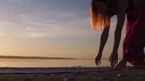 关闭在沙子的一张信奉瑜伽者妇女展开瑜伽席子在水附近 太阳发光 早晨黄昏 股票录像