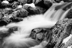 关闭在河溪的岩石在流动在长的曝光的缎花露水 免版税图库摄影