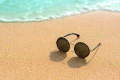 关闭在海滩的太阳镜并且弄脏蓝色海 库存照片