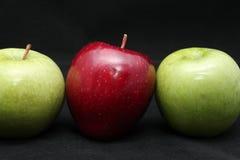 关闭在深黑色背景的三个新鲜的发光的绿色和红色苹果 图库摄影