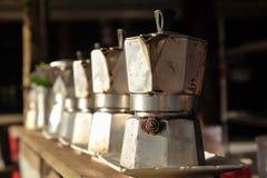关闭在火炉的咖啡罐老铝开放早餐早晨市场与阳光 免版税图库摄影
