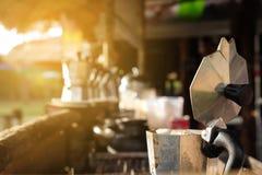 关闭在火炉的咖啡罐老铝开放早餐早晨市场与阳光 库存图片