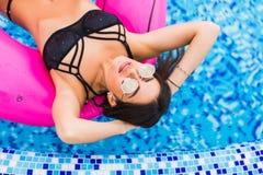 关闭在火鸟的美好的性感的女孩游泳在太阳镜的水池 夏天职业 免版税库存照片