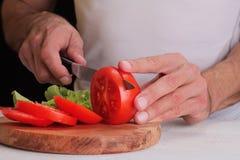 关闭在烹调蕃茄汤,意大利面条酱的人人 冷却在家,健康生活方式,饮食食物 库存照片