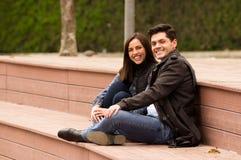 关闭在爱的一对美好的微笑的年轻夫妇在st情人节和看照相机,坐在公园 免版税库存照片