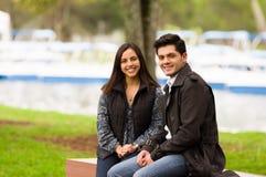 关闭在爱的一对美好的微笑的年轻夫妇在st情人节和看照相机,坐在公园 库存图片