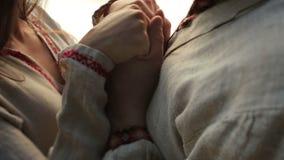 关闭在爱的美好的夫妇在软软地握在码头的传统乌克兰衣裳手在山湖 影视素材