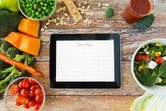关闭在片剂个人计算机和菜的饮食计划 免版税库存照片