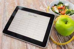 关闭在片剂个人计算机和食物的饮食计划 免版税库存图片