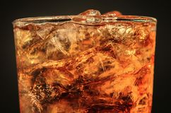 关闭在玻璃和泡影苏打的冰可乐在黑色 库存图片