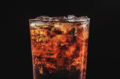 关闭在玻璃和泡影苏打的冰可乐在黑色 免版税库存照片