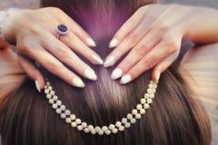 关闭在珍珠的妇女手 免版税库存图片