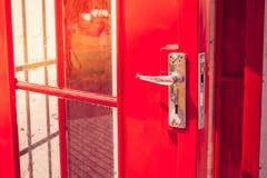 关闭在电话亭的被打开的红色现代门的银色金属门把手 图库摄影