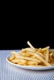 关闭在白色板材的油煎的炸薯条 免版税库存图片