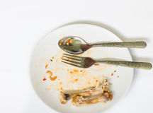 关闭在白色盘的鸡骨头用用浪费的食物 免版税库存照片
