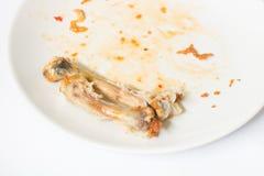 关闭在白色盘的鸡骨头用用浪费的食物 免版税库存图片
