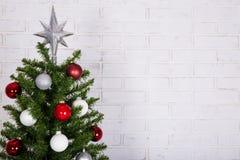 关闭在白色砖墙的圣诞树 免版税图库摄影