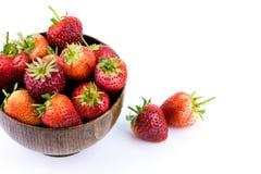 关闭在白色背景隔绝的一个木碗的新鲜的草莓果子 免版税库存图片
