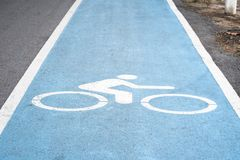 关闭在白色自行车标志或象在蓝色自行车车道与wh 图库摄影