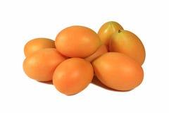 关闭在白色隔绝的堆明亮的橙黄色成熟玛丽亚李子 库存图片