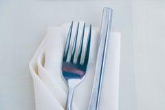关闭在白色餐巾的叉子在餐馆 库存照片