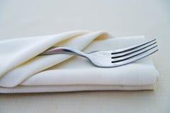 关闭在白色餐巾的叉子在餐馆 库存图片