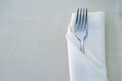 关闭在白色餐巾的叉子在餐馆 免版税库存照片