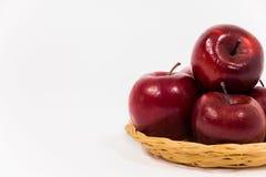 关闭在白色b隔绝的柳条筐的成熟红色苹果 图库摄影