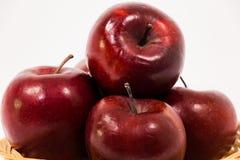 关闭在白色b隔绝的柳条筐的成熟红色苹果 库存照片