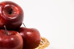 关闭在白色b隔绝的柳条筐的成熟红色苹果 库存图片