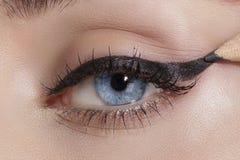 关闭在眼睛,做五颜六色的眼影膏和眼线膏 免版税库存图片