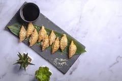 关闭在石板岩的新煮沸的dumplingss 与芝麻籽的中国饺子在一片绿色叶子 妇女吃 库存图片