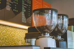 关闭在磨咖啡器的咖啡豆准备的能研咖啡在葡萄酒样式的咖啡店 免版税库存照片