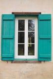 关闭在窗口在老农厂房子一个米黄门面的被打开的土气绿松石老快门  免版税库存图片