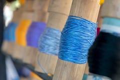 关闭在竹管附近被聚焦被包裹的蓝色毛线 免版税库存照片