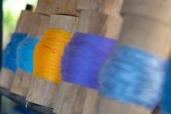 关闭在竹管附近被聚焦被包裹的黄色毛线 库存图片