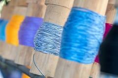 关闭在竹管附近被聚焦被包裹的黑和软的蓝色毛线 免版税图库摄影