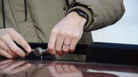 关闭在米黄附头巾皮外衣紧固螺丝的一个年轻男性有在汽车栏杆机架的一把棘轮扳手的 股票录像