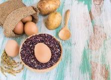 关闭在粗麻布大袋和紫色米莓果的鸡蛋在木后面 免版税库存图片