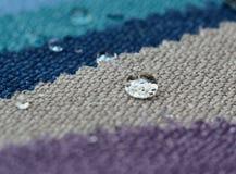 关闭在粗麻布纺织品样品的水下落 容易的干净,防水表面的概念 库存图片