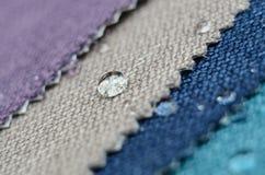关闭在粗麻布纺织品样品的水下落 容易的干净,防水表面的概念 图库摄影