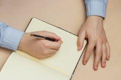 关闭在纸笔记本或老日志的偶然人文字 图库摄影