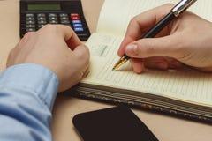 关闭在纸笔记本或老日志的偶然人文字 免版税库存照片
