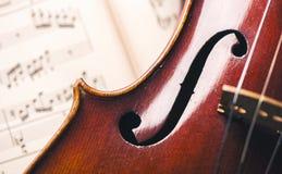 关闭在纸笔记的一把老小提琴 免版税库存图片